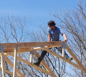 Spanning two trusses, Jonas nails in place the top brace beam