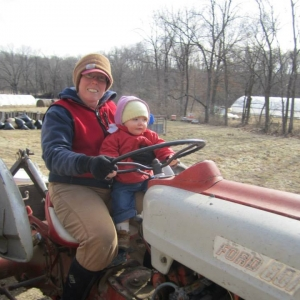 Sylvia helping drive Jolene the tractor
