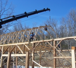 The crane sets in place the next truss
